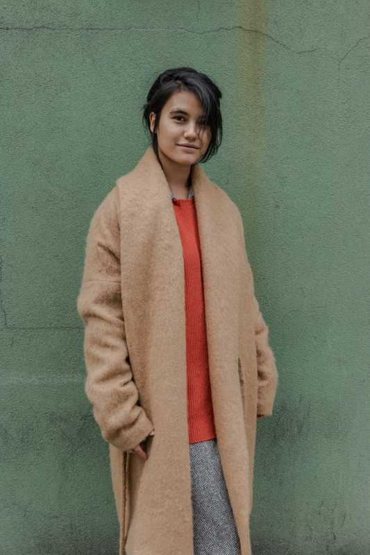 Camel side-tie coat and orange ribbed cashmere sweater