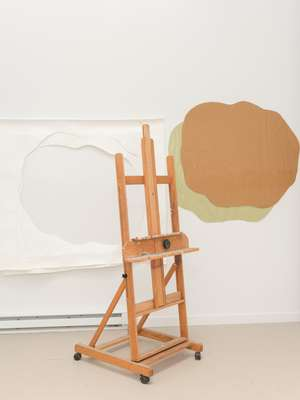 Easel with artwork in the background