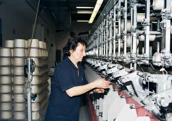 Employee twisting the threads during the spinning process