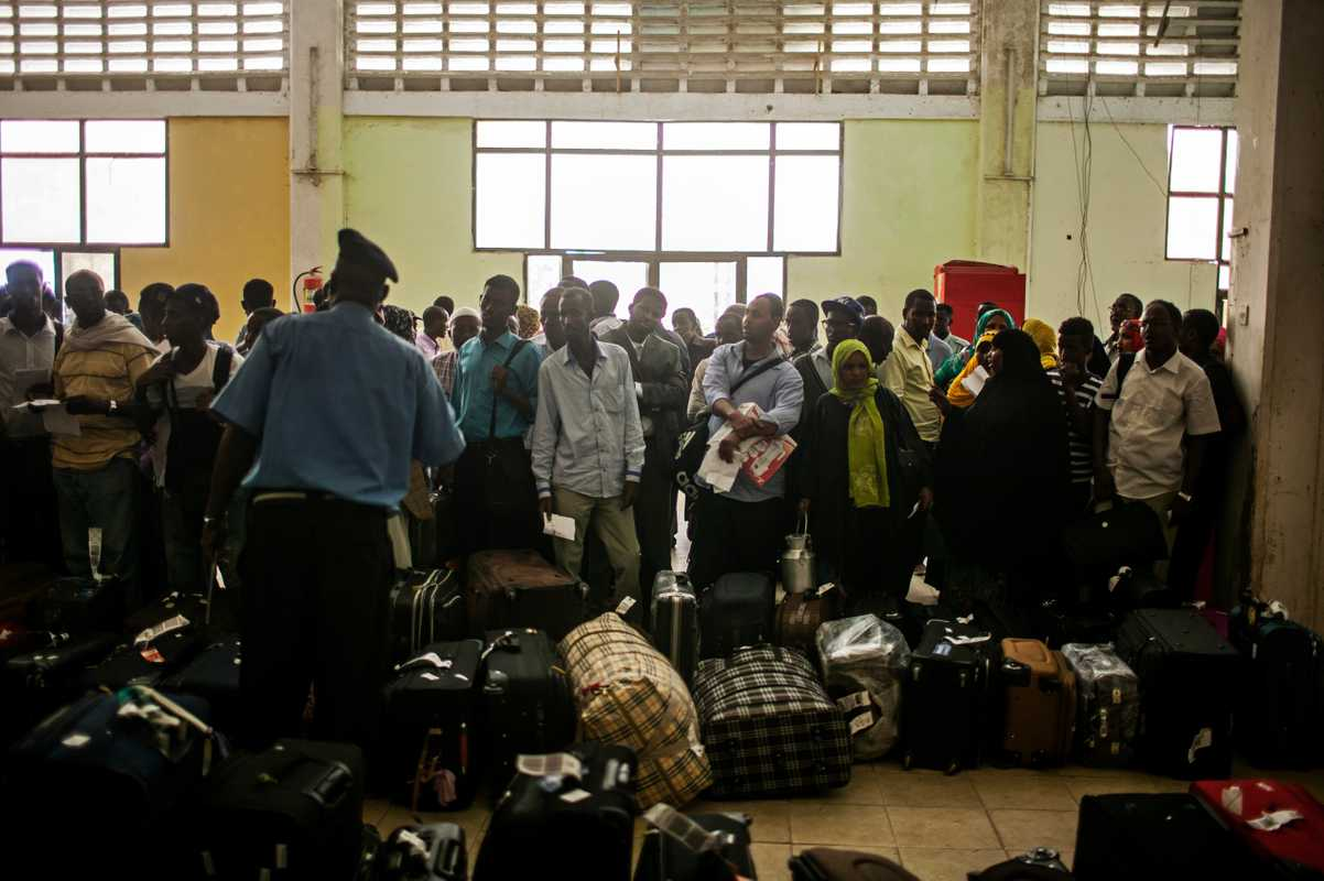 Recently arrived passengers wait to collect their luggage