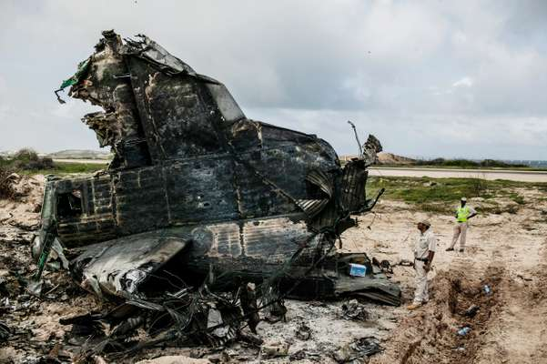 Sean Mendis, SKA station manager, next to the wreckage of an Ethiopian Air Force flight that crash-landed on 9 August 2013. The plane was carrying some 15 tonnes of ammunition destined for international forces in Somalia