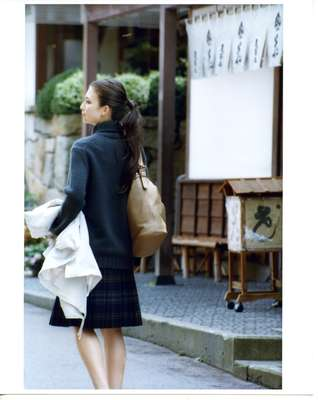 Jumper by Drawer, skirt by Prada, coat (carried) by Knott from Tomorrowland, bag by Jimmy Choo