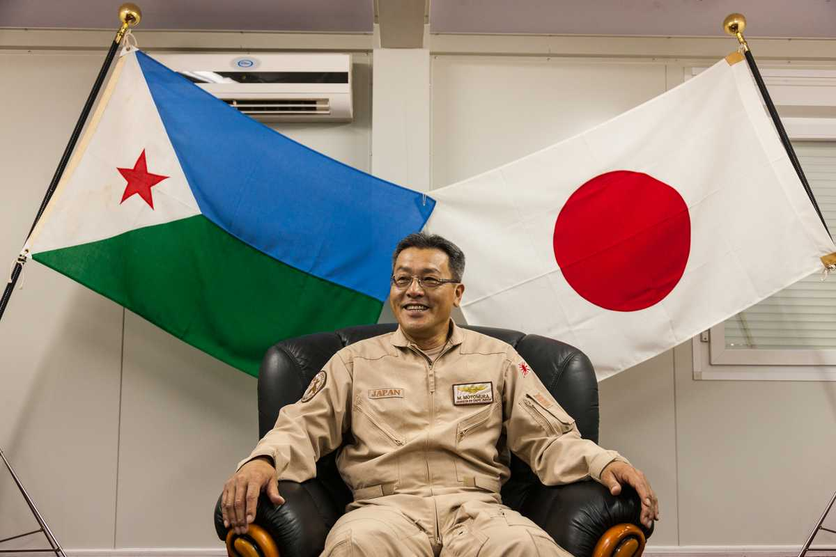 Airforce captain and commanding officer of the counter-piracy mission's air-support unit Masahisa Motomura beneath the flags of Djibouti and Japan