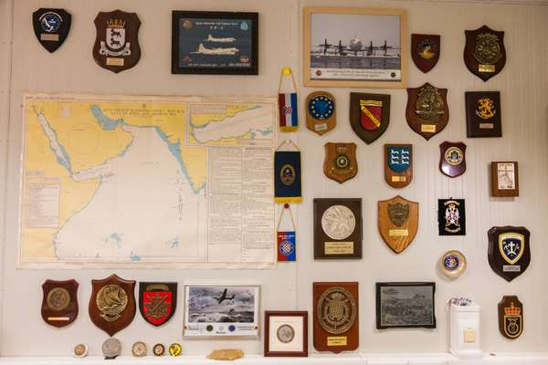 Squadron and regimental badges adorn a wall in the office of the EU mission commander