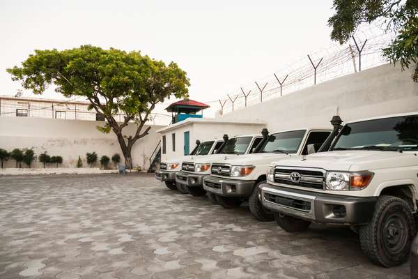 Toyota Land Cruisers line the inside of the compound