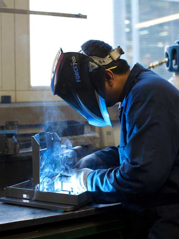 Folding and welding: workers fold and weld the pieces together to create the machine's shell