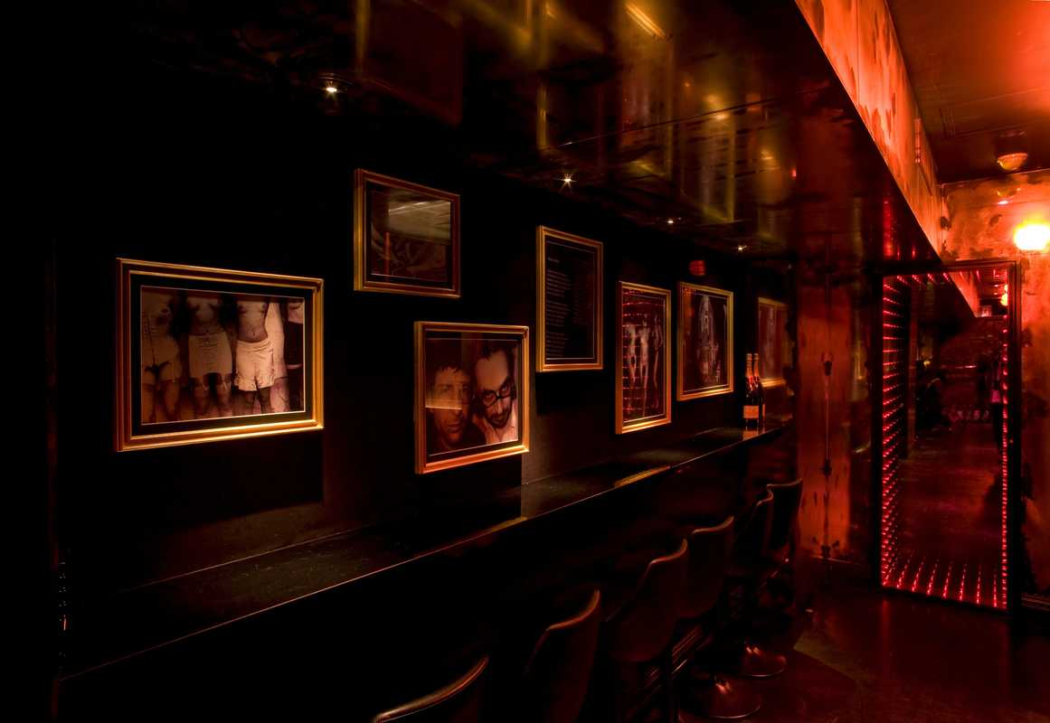 Sparkling mirrors and black-and-white photos line the black walls of the club's long corridor