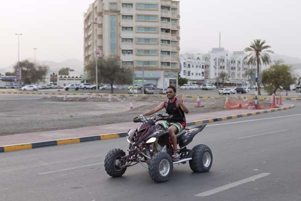 A man drives down the corniche on an all terrain vehicle