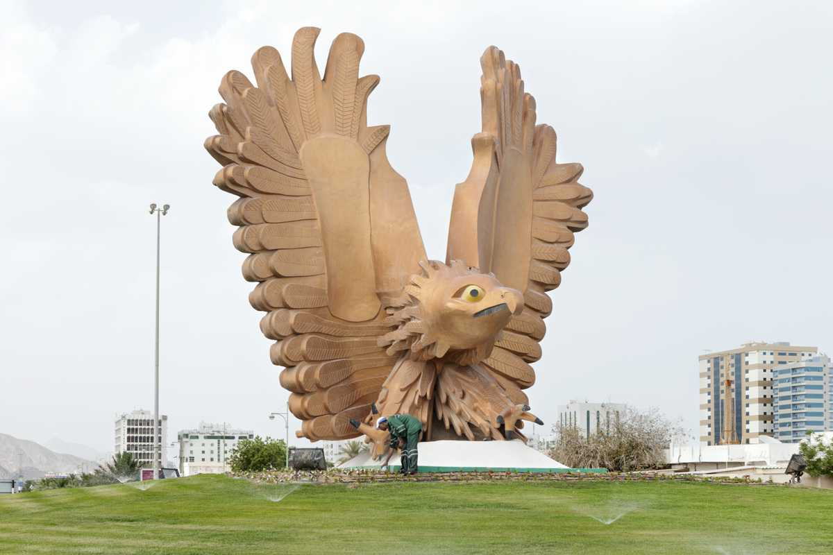 A man turns on the sprinklers at a falcon statue at a roundabout in Fujairah