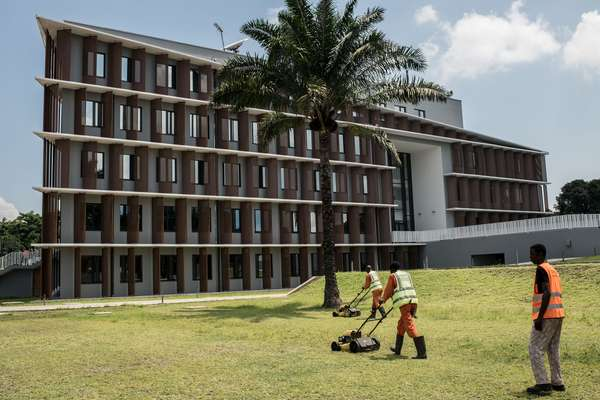 Congolese workers mowing the lawn at the new Belgian embassy in Kinshasa