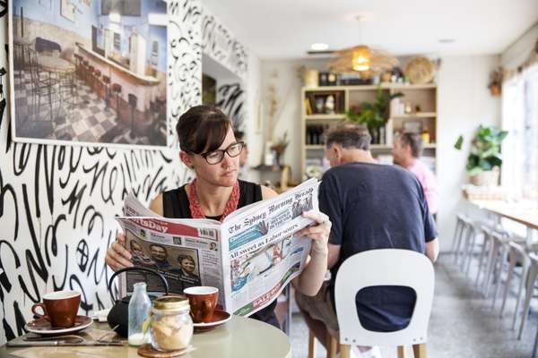 Reading the 'Herald' at the Fine Food Cafe