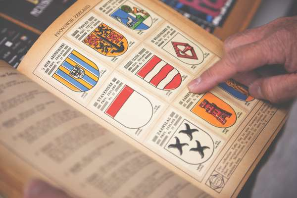 Staff flip through a vintage book of Dutch crests for new ideas