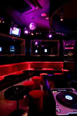 Seating 24 people, Amour's Room C features red velvet tables, a DJ booth and a glass stage surrounded by mirrors