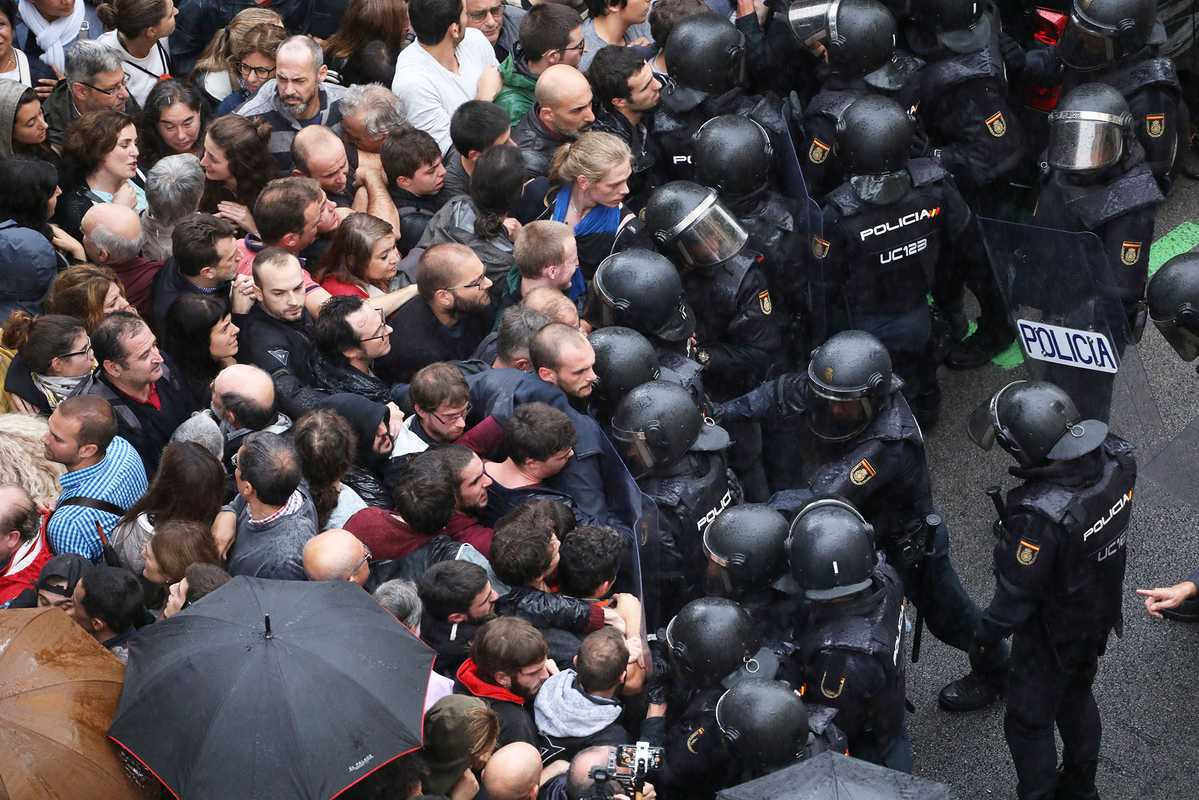 Police face off with demonstrators outside a polling station, in Barcelona, Spain, 1 October 2017