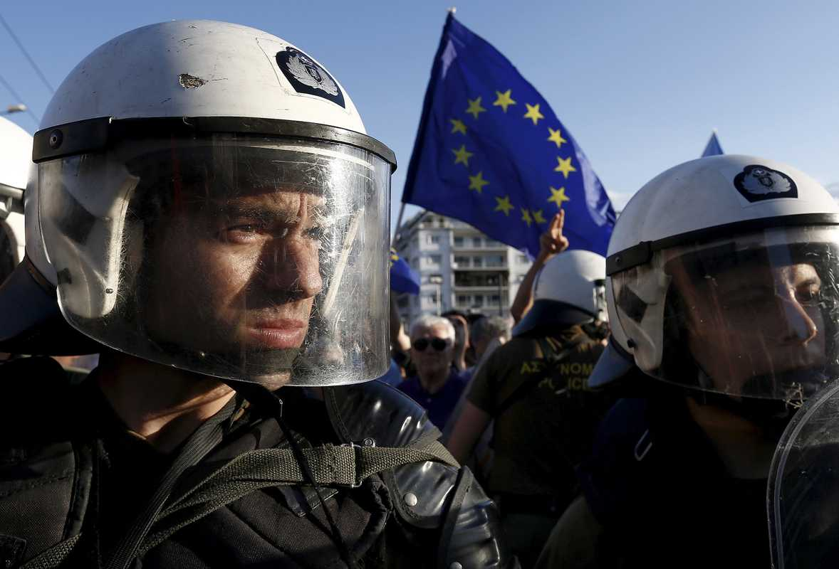 22 June 2015: Riot police standing between  anti-austerity and pro-EU protesters in Athens, Greece