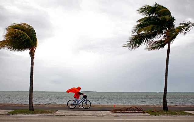 8 September 2008: woman walking her bicycle on an island in the Florida Keys during Hurricane Ike