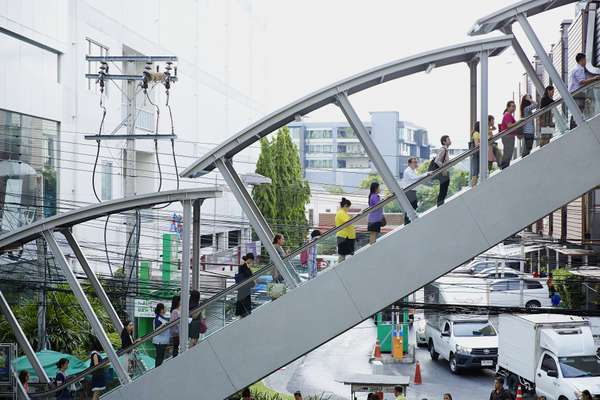 Commuters ascend to Ari's Skytrain platform