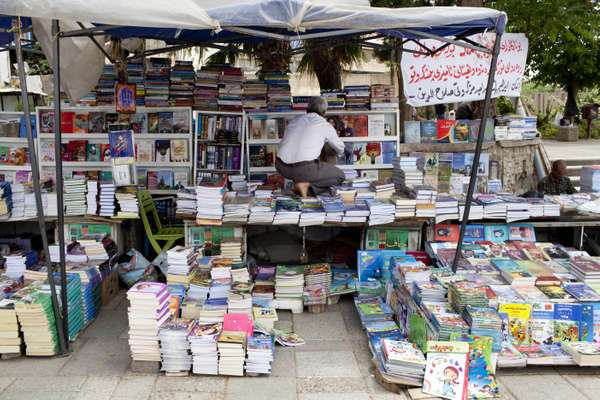 Bookseller arranging his stall in the bazaar