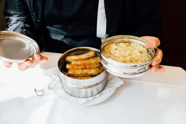 Takeaway lunchbox – presented to Wenders during the meal – of sausages with sauerkraut and mustard