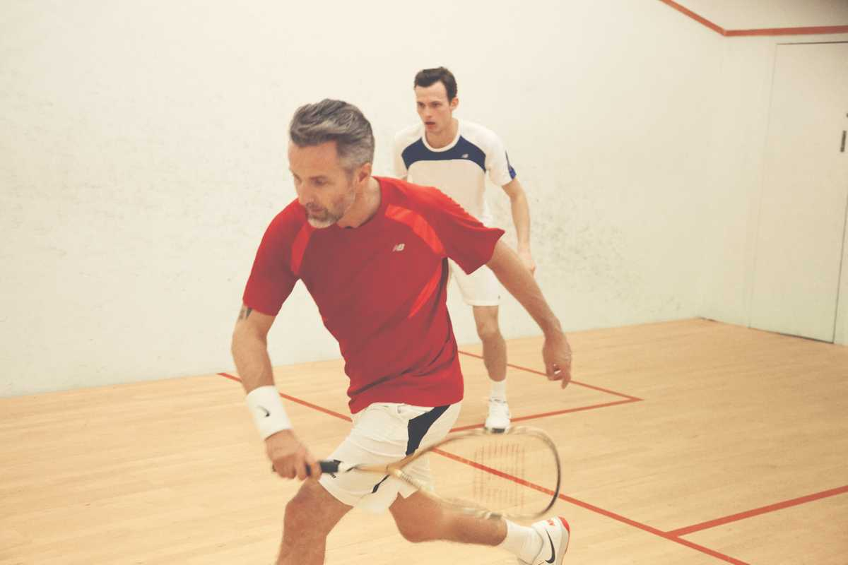 Ben wears red t-shirt by New Balance, shorts by Lotto, wristband and shoes by Nike, racquet by Wilson