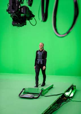 Walking on a green treadmill, which simulates walking in a virtual environment