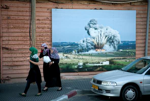 Conservative Palestinian Women in Jaffa's old port walk in front of a public photo exhibition