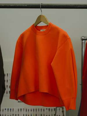 Orange sweater hanging in-store