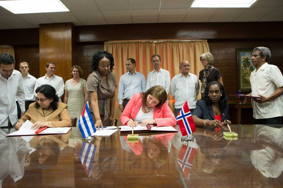Gry Larsen (centre) signs a co-operation deal with Cuba and Haiti