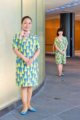 Guides wear dresses designed by Akira Minagawa, featuring the tower motif
