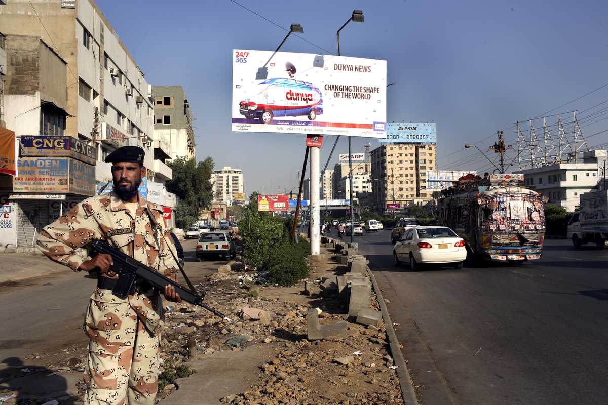 Pakistani ranger guards beneath a TV news billboard on a Karachi street