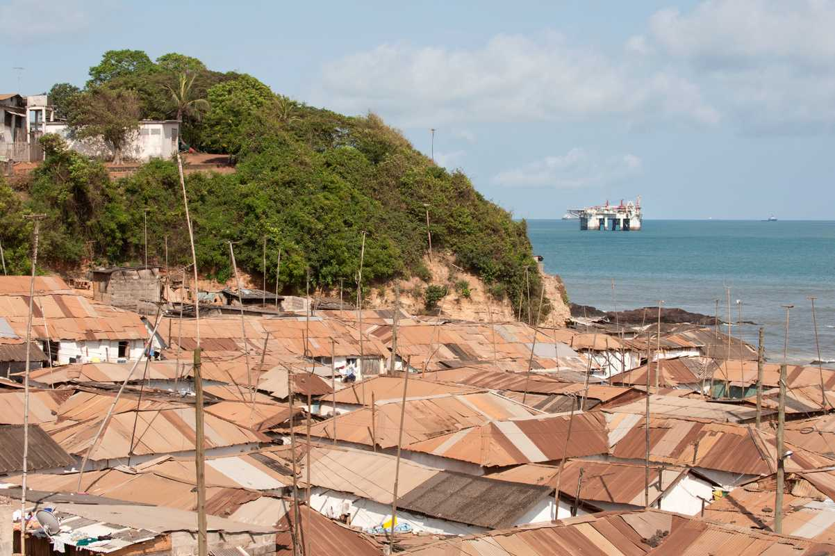 Roofs of Takoradi with view of off-shore oil rig