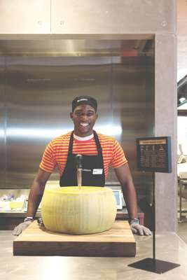 An employee about to crack into a wheel of Parmesan