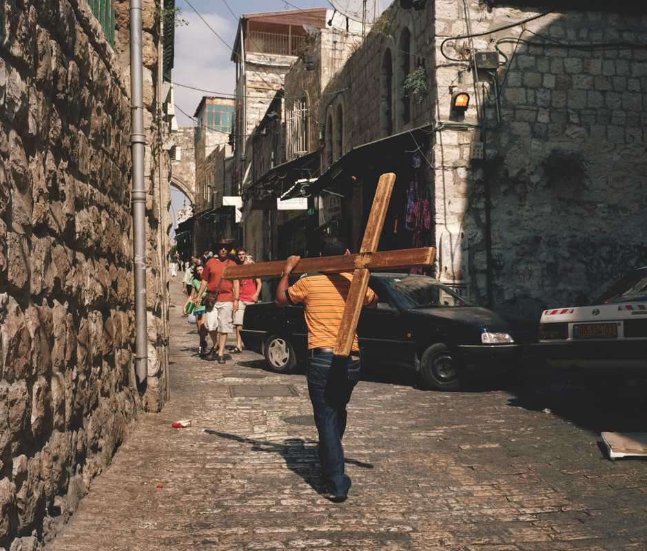 A man carries a crucifix through old Jerusalem, following Jesus's path prior to his crucifixion
